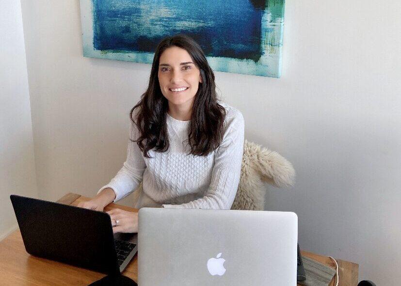 COVID survivor Claudia Kiss sitting at desk