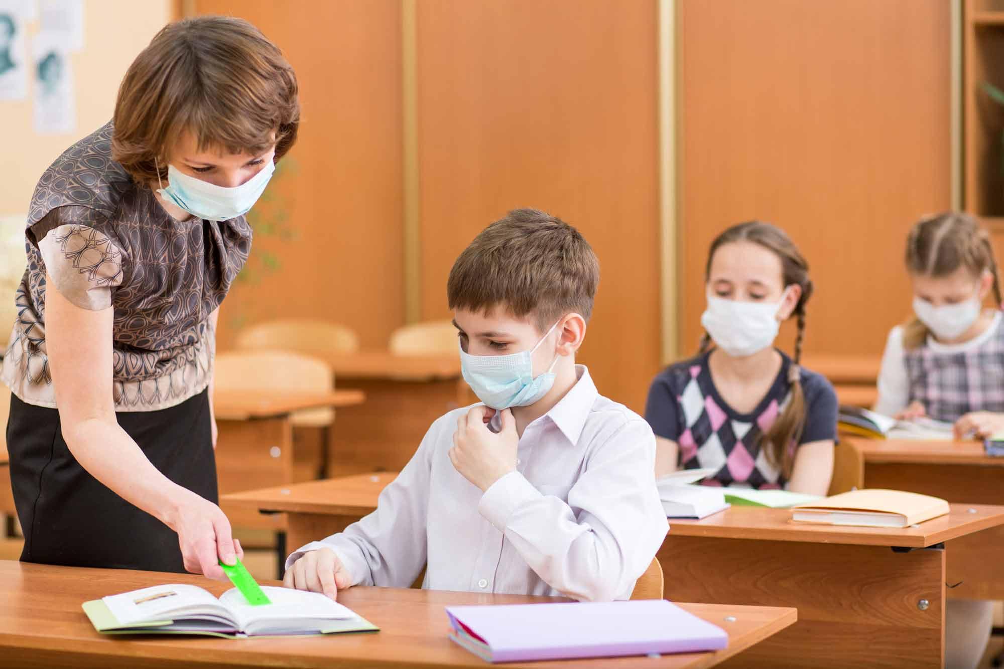 maestro enmascarado y estudiantes en el aula de la escuela