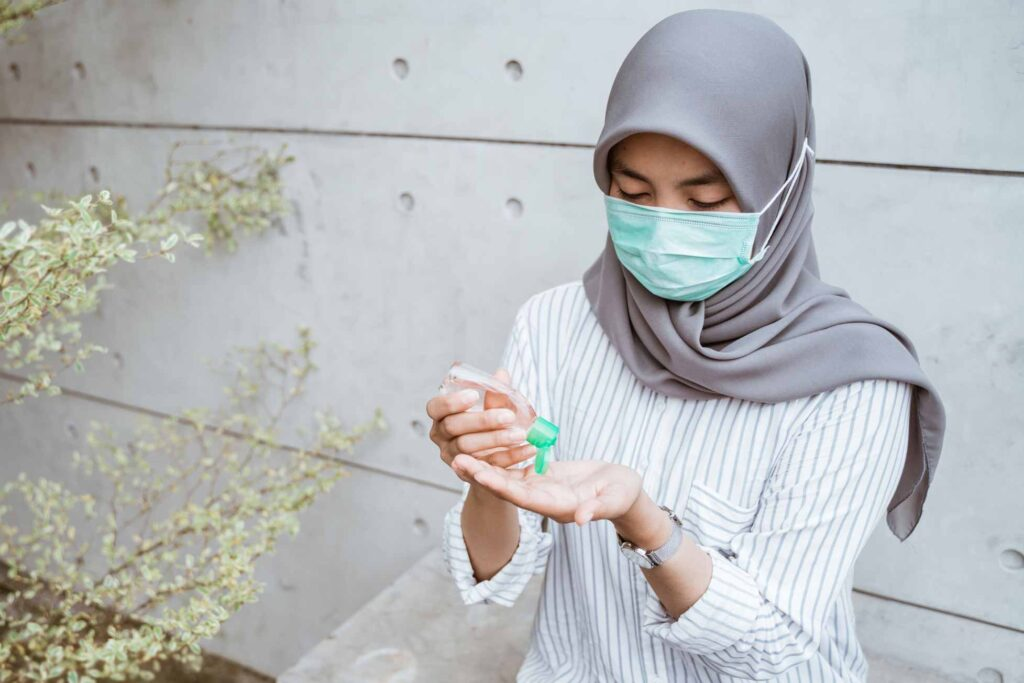 woman in mask applying hand sanitizer