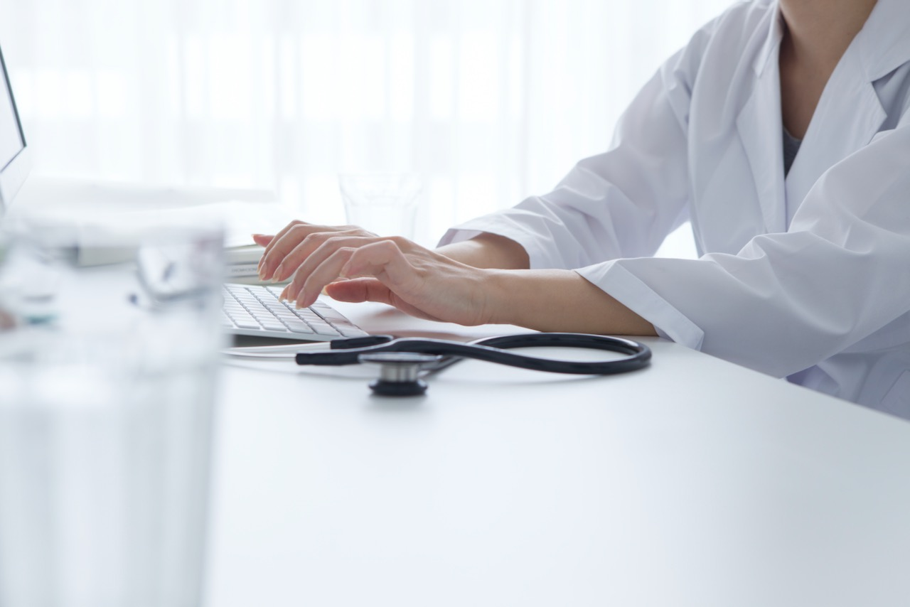 Doctor in a white lab coat is seated and typing at a computer