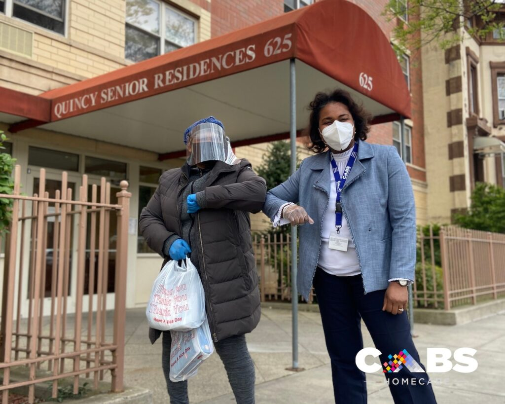 Woman in face shield holding a bag of PPE bumps elbows with a woman in a blazer and a white face mask under a red awning that reads 'Quincy Senior Residences.'